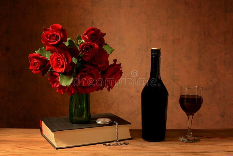 Rosas en un florero, libros y vino fotos de archivo