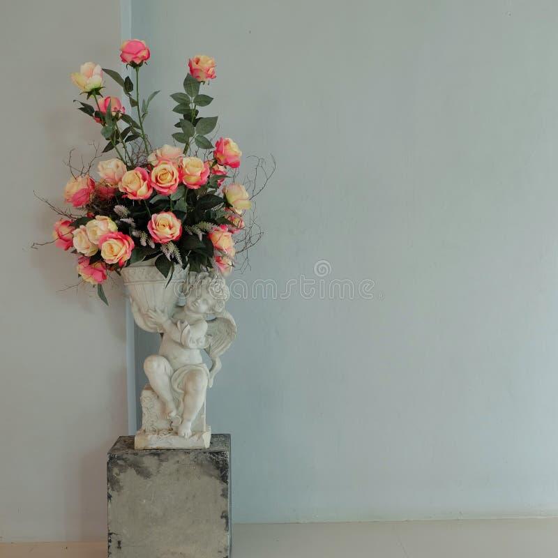 Rosas falsificadas nos cupidos bonitos vaso & na luz - parede azul fotos de stock