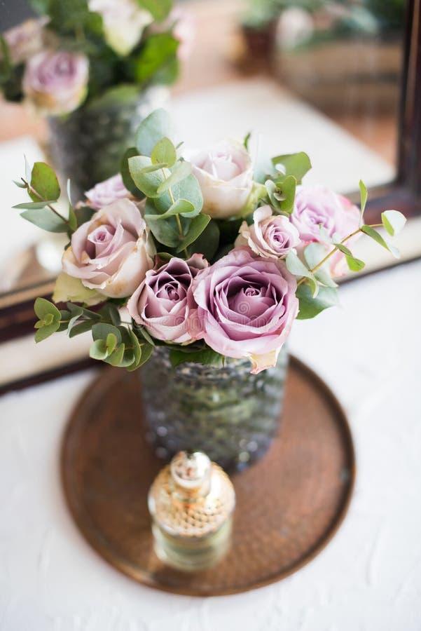 Rosas frescas do verão da cor roxa, malva no vaso e perfume pelo th fotografia de stock