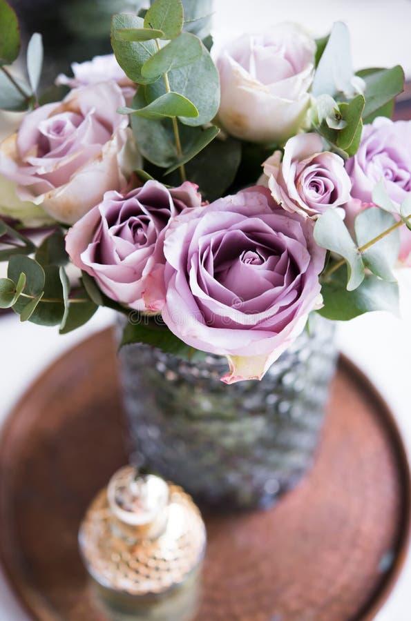 Rosas frescas pasteis do verão da cor roxa, malva no vaso no cl da bandeja fotografia de stock