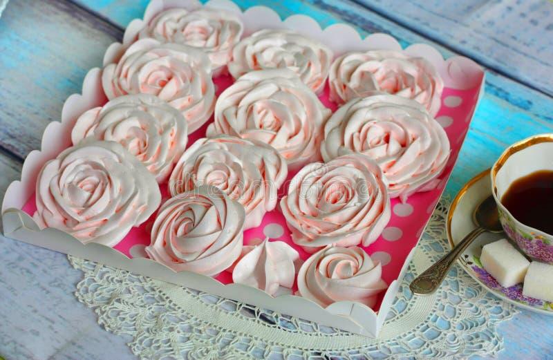 Rosas merengue numa caixa e uma xícara de chá fotos de stock royalty free
