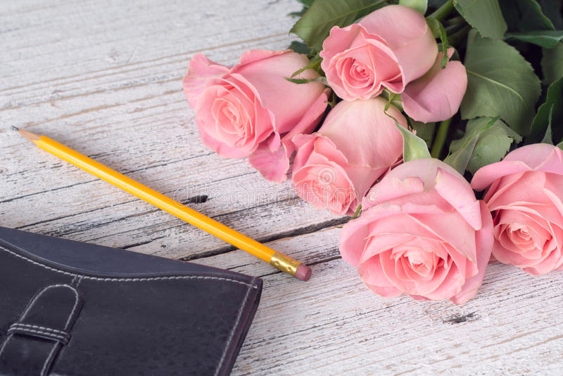 Rosas, pensil e caderno cor-de-rosa bonitos imagem de stock royalty free