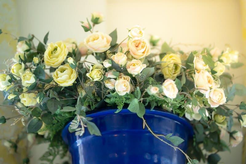 Rosas plásticas coloridas del rosa y blancas un ramo de potes azules colocados en el gabinete en la casa imagen de archivo libre de regalías