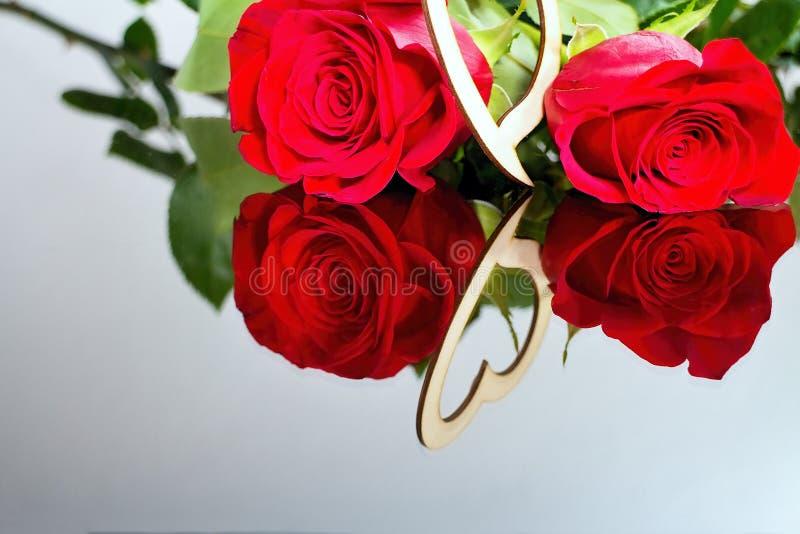 Rosas rojas con el corazón con la reflexión en espejo Valentine& x27; tema del día de s Momentos románticos fotos de archivo libres de regalías