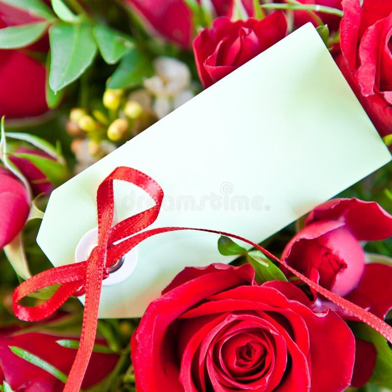Rosas rojas con una tarjeta en blanco imagen de archivo libre de regalías