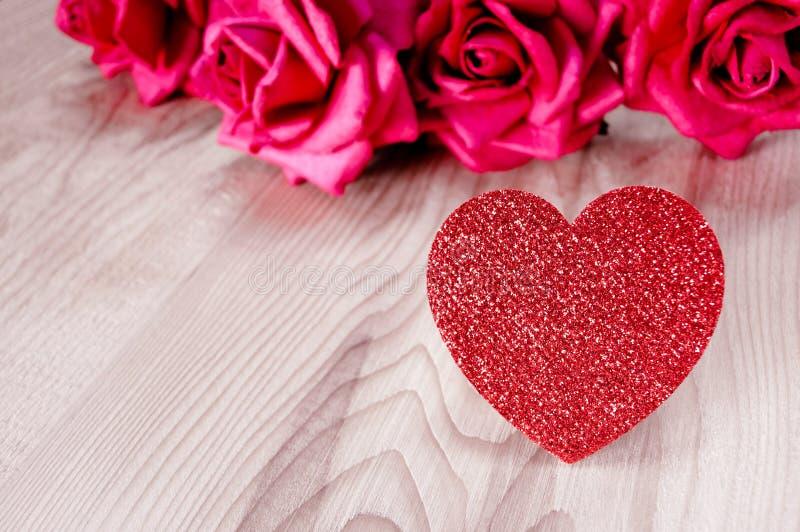 Rosas rojas, corazón rojo en la tabla de madera con el blackground negro puede utilizar conveniente para la ocasión especial día  imagen de archivo