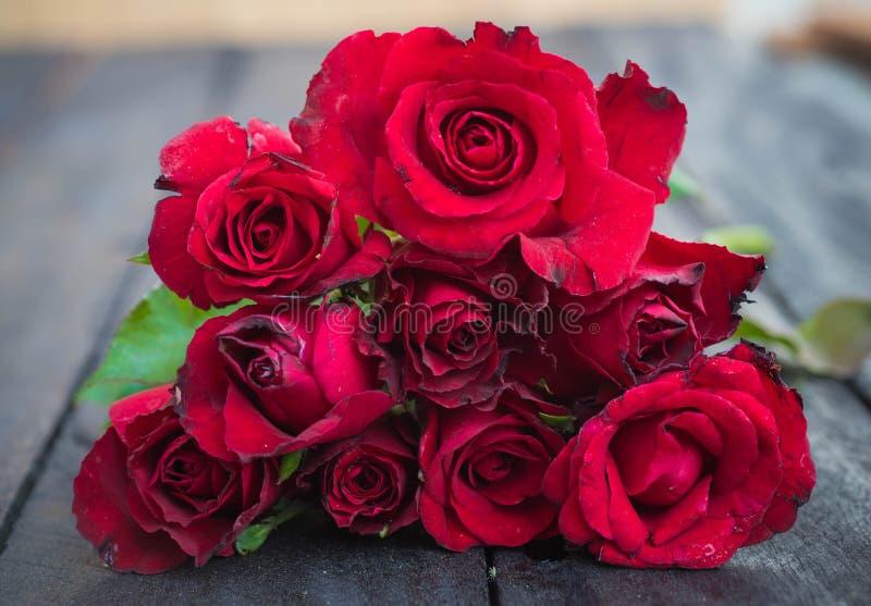 Rosas rojas en el fondo de madera, vintage retro, foto de archivo