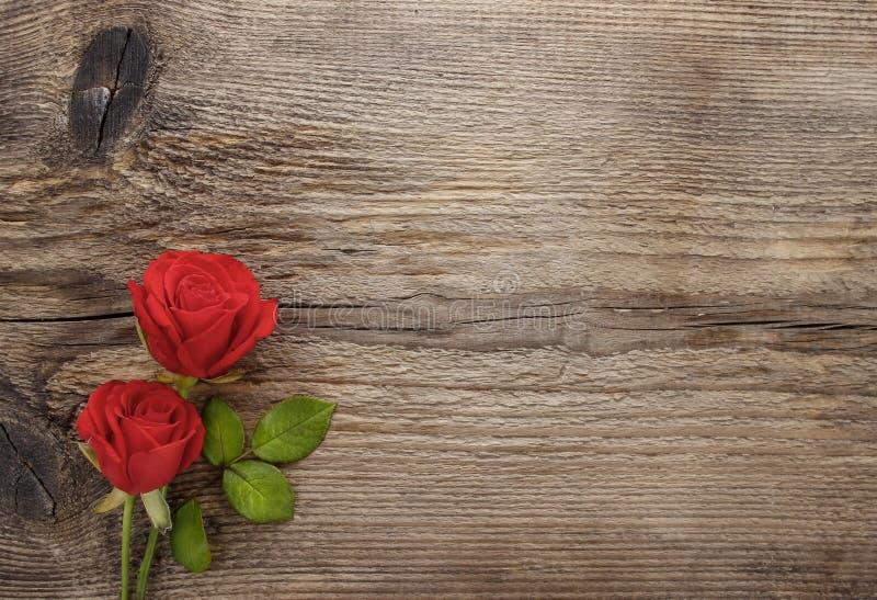 Rosas rojas en la tabla de madera imagen de archivo