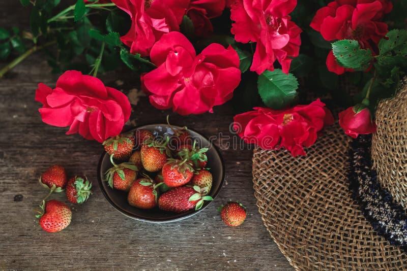 Rosas rojas, fresas y un sombrero en una tabla vieja fotografía de archivo