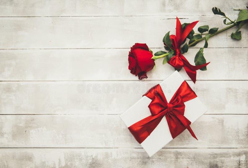 Rosas rojas y caja de regalo en una tabla de madera Día de tarjetas del día de San Valentín feliz imagenes de archivo