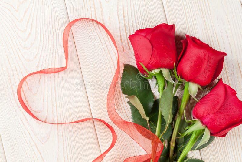 Rosas rojas y corazón del día del ` s de la tarjeta del día de San Valentín fotografía de archivo libre de regalías