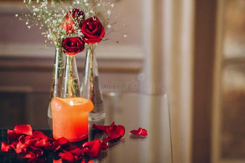 Rosas rojas y pétalos ardientes del ingenio de la vela en la tabla de cristal Lujo d imagen de archivo