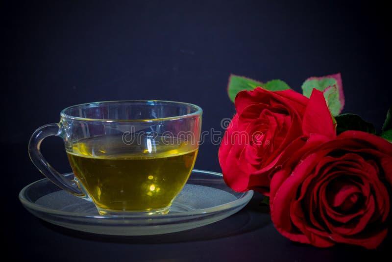 Rosas rojas y té en vidrio fotografía de archivo