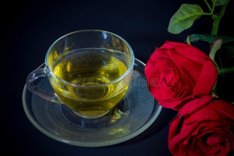 Rosas rojas y té en vidrio imágenes de archivo libres de regalías