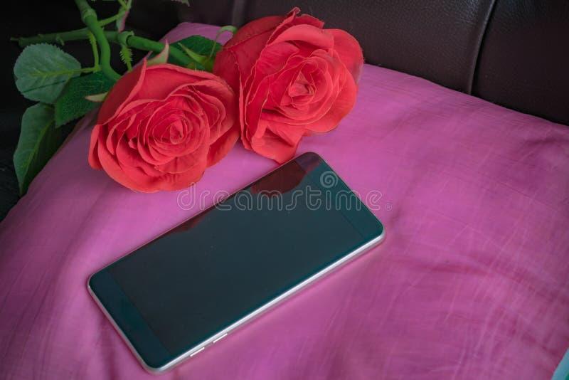 Rosas rojas y teléfonos imágenes de archivo libres de regalías