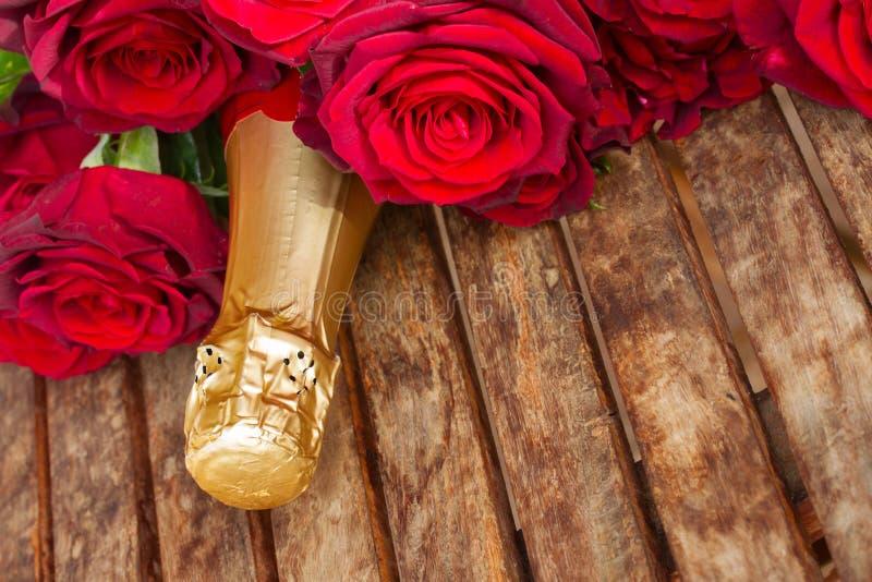 Rosas rojo oscuro con el cuello del champán imágenes de archivo libres de regalías