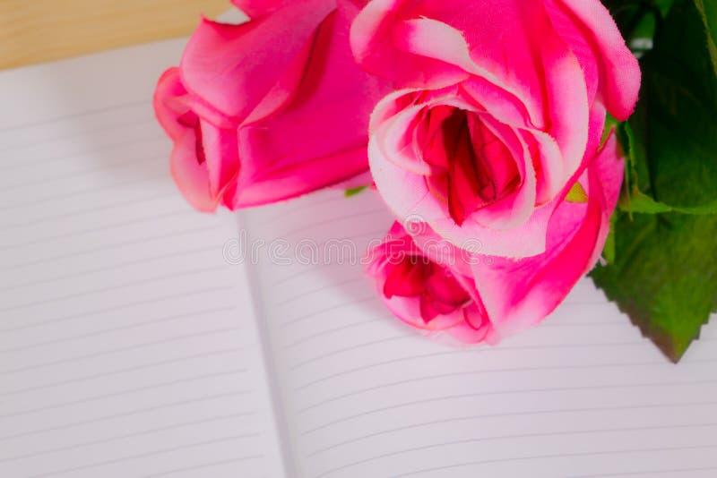 Rosas rosadas en las notas de libro imagen de archivo libre de regalías