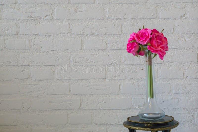 Rosas rosadas en un florero de cristal en una pared de ladrillo blanca, día de San Valentín o un fondo interior fotografía de archivo libre de regalías