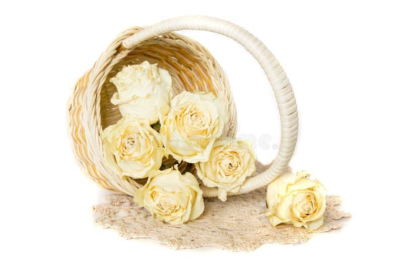 Rosas secadas en cesta con el tapetito foto de archivo