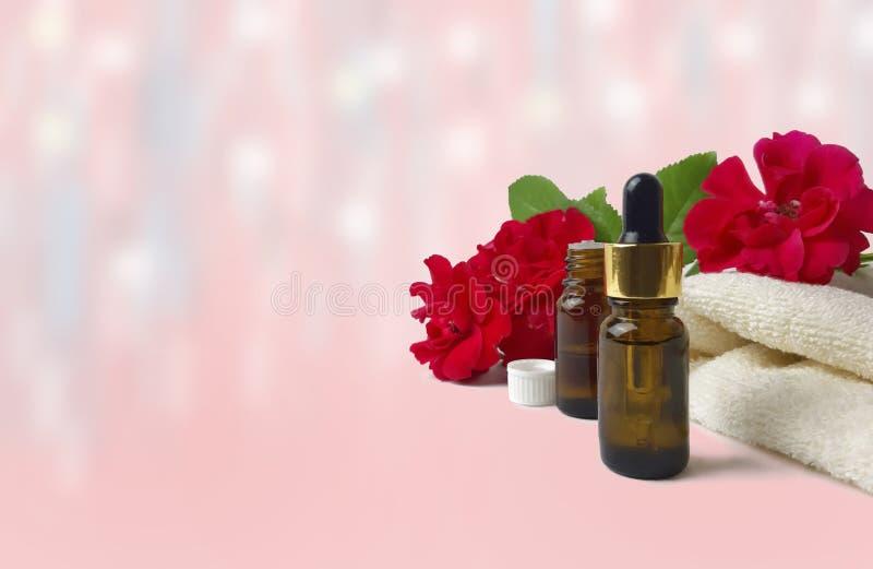 Rosas, toalla, botella de aceite esencial en fondo rosado fotos de archivo