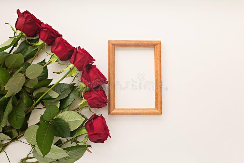 Rosas vermelhas em um fundo claro e em um quadro para uma foto imagens de stock royalty free