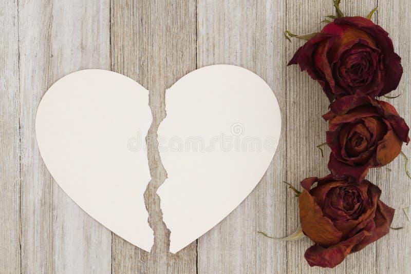 Rosas vermelhas inoperantes com o cartão rasgado da coração-forma na madeira resistida para trás foto de stock royalty free