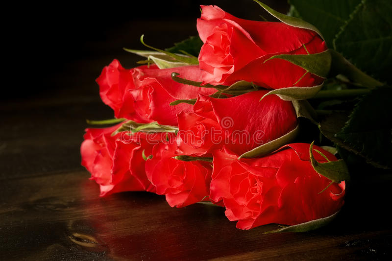 Rosas vermelhas no assoalho de madeira fotografia de stock