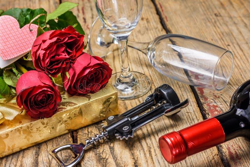 Rosas vermelhas, uma garrafa do vinho e caixa de presente Dia do `s do Valentim foto de stock royalty free