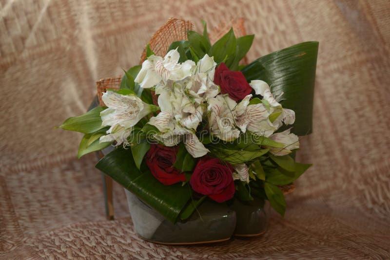 Rosas y flores rojo oscuro en los zapatos verdes en el talón imágenes de archivo libres de regalías