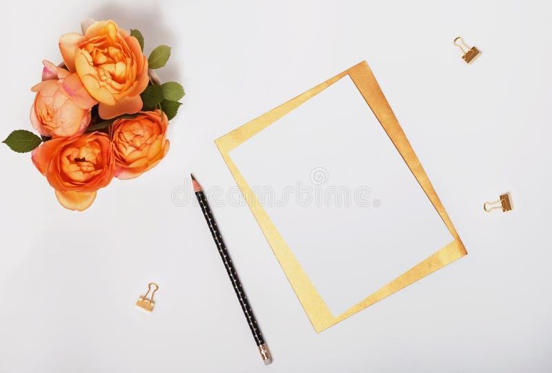 Rosas y opinión superior del papel en blanco imagen de archivo