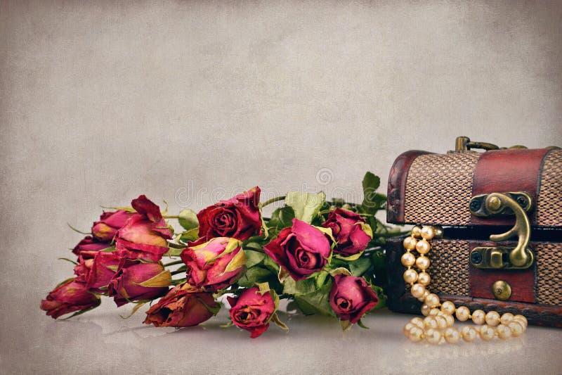 Rosas y perlas secas en cofre del tesoro fotos de archivo