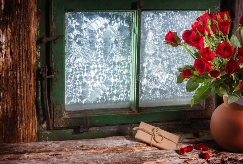 Rosas y regalo en ventana foto de archivo