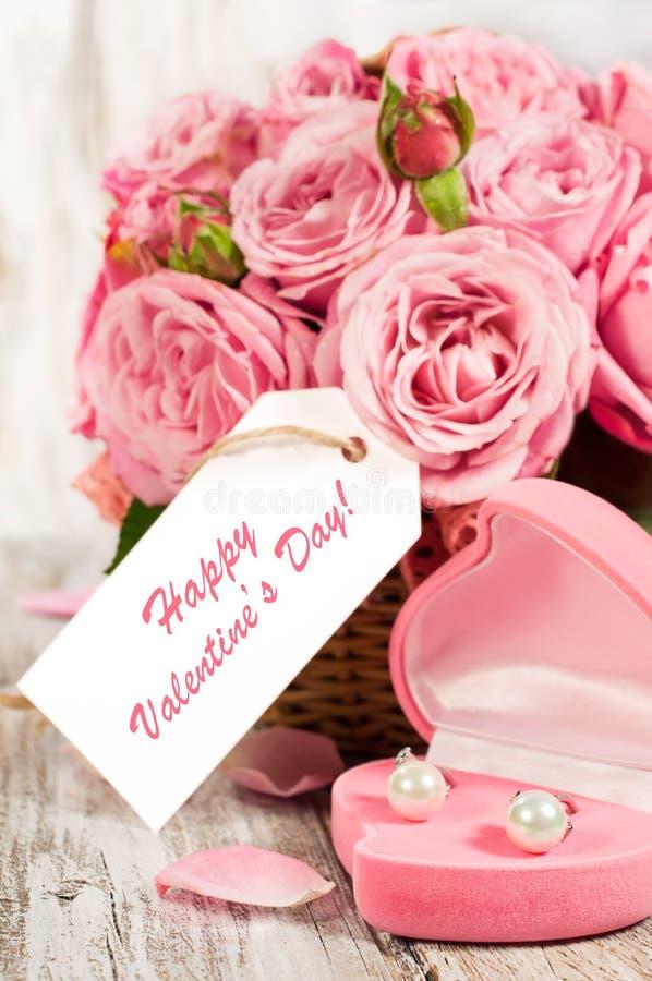 Rosas y regalo rosados en una cesta imagenes de archivo