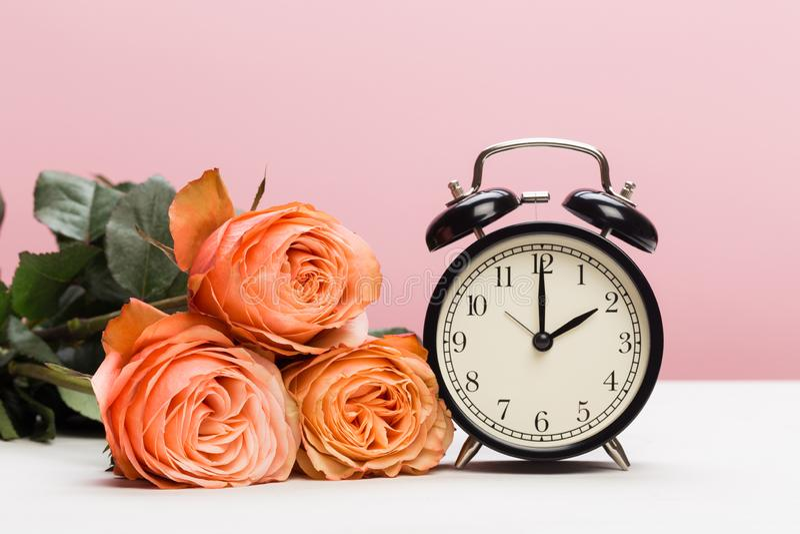 Rosas y reloj de Rose en el fondo rosado, ahorro de luz del día foto de archivo libre de regalías