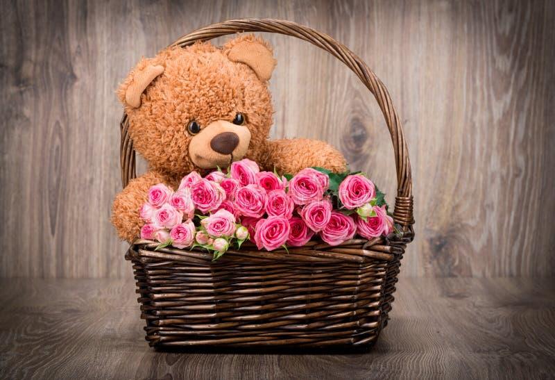 Rosas y un oso de peluche imagenes de archivo