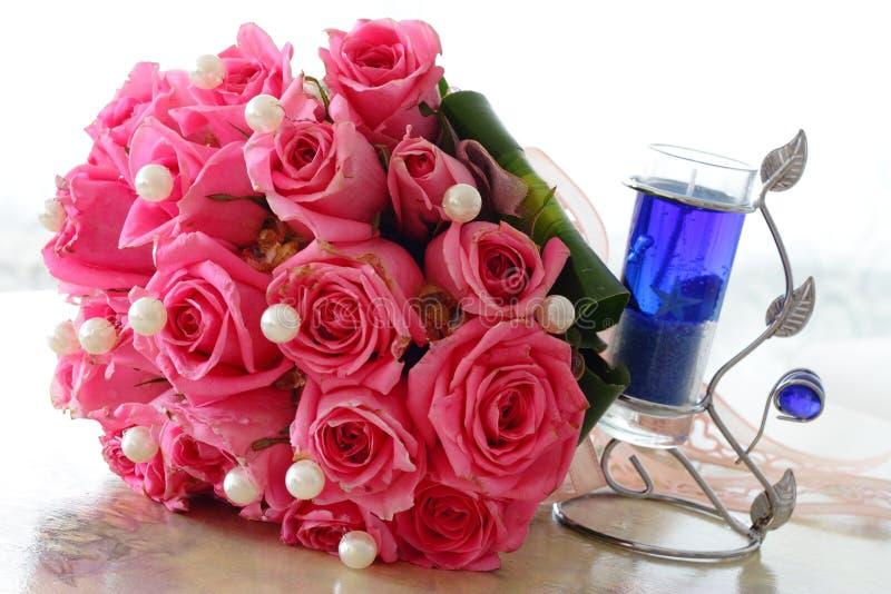 Rosas y vela imagenes de archivo