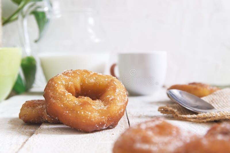 Rosca o ciambelle spagnole a colazione su un tavolo di legno bianco accanto a una tazza di caffè e un barattolo di latte Sfondo b immagine stock libera da diritti