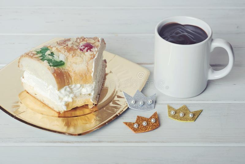 Roscon de reyes, spanish three kings cake next to a cup with chocolate royalty free stock photos