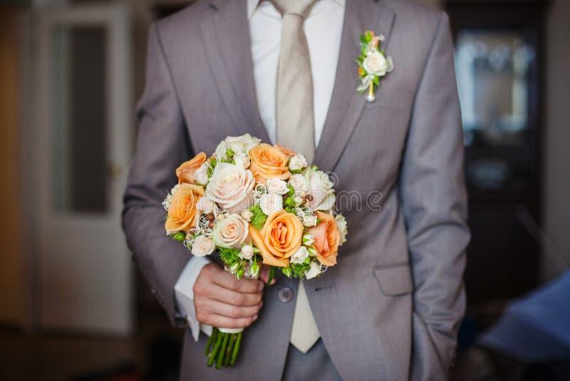Rose arancio e beige del mazzo nuziale con la maniglia fotografia stock