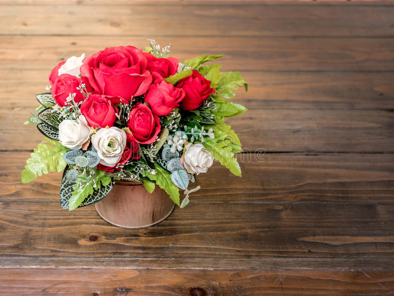 Rose artificial flowers in the pot , on the wood desk stock images