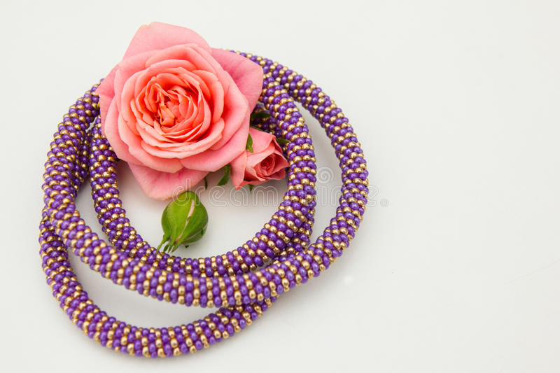 Rose and bead cord. Rose in the yellow and violet bead cord circle royalty free stock photography