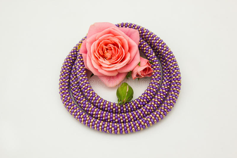 Rose and bead cord. Rose in the yellow and violet bead cord circle royalty free stock photos