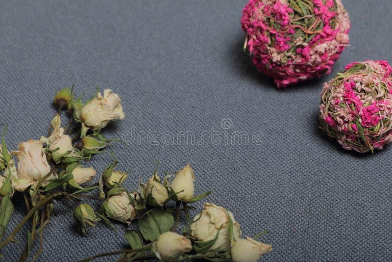 Rose beige secche Contro lo sfondo di struttura approssimativa del tessuto grigio Vicino sono due palle decorative di erba secca  immagini stock