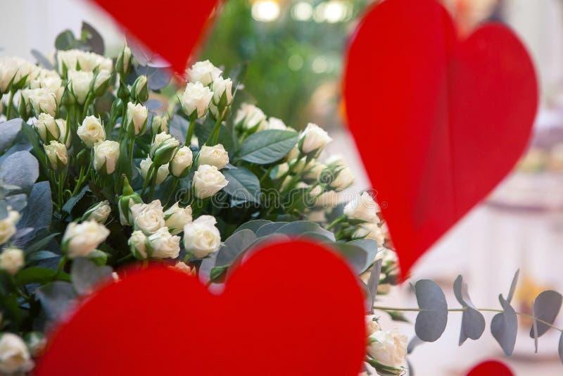 Rose bianche e decorazione rossa dei cuori immagine stock