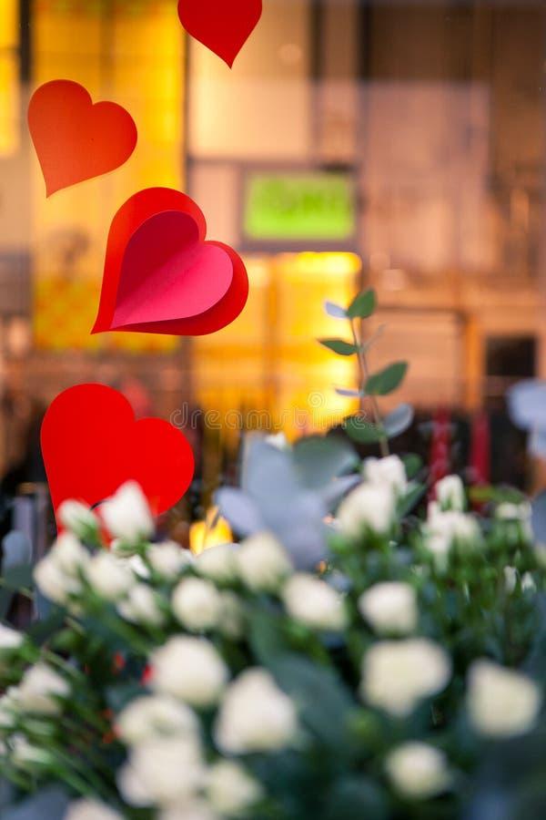 Rose bianche e decorazione rossa dei cuori immagini stock