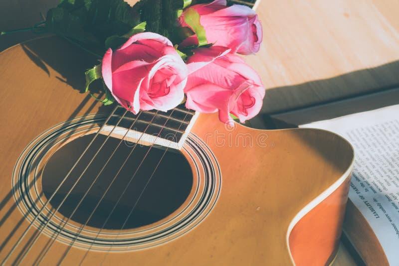 Rose blüht auf einem Buch mit einer Gitarre stockfoto