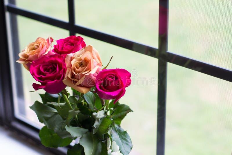 Rose Bouquet durch Fenster stockfotos