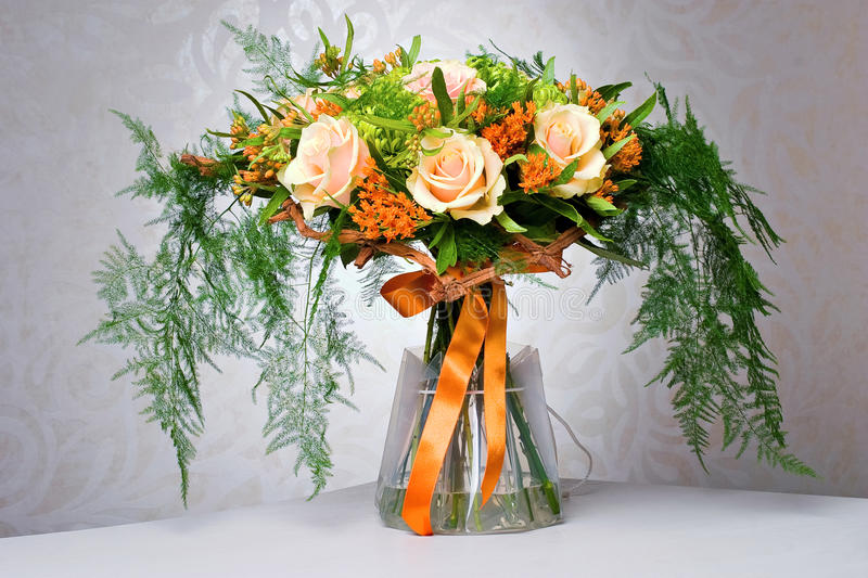 Rose Bouquet on Table. Rose bouquet with orange ribbon in vase stock photos
