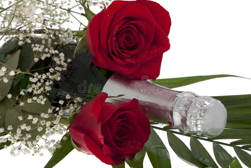 Rose con la bottiglia del champagne immagine stock