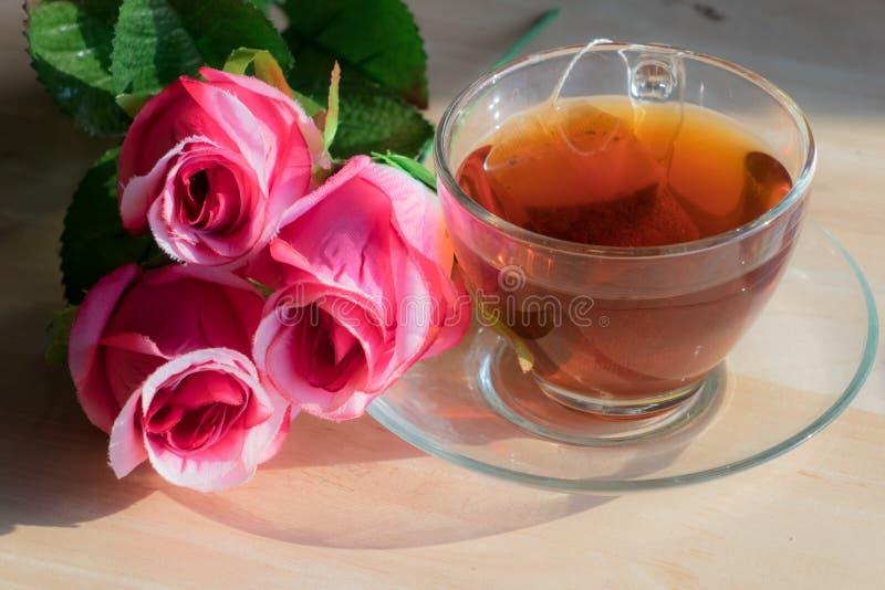 Rose con té caliente en una tabla de madera foto de archivo